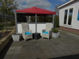 een heerlijk terras in de zon met luxe stoelen en tuinkussens
